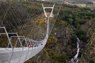 People walk on the world's longest pedestrian suspension bridge '516 Arouca', in Arouca