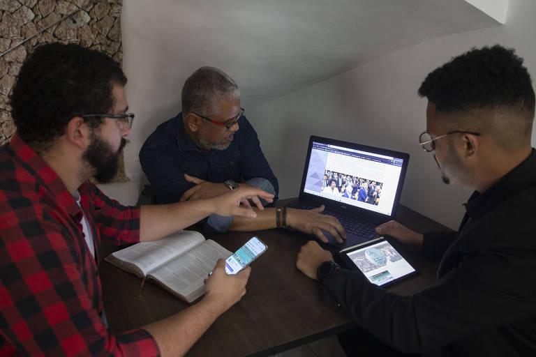 Três homens sentados à mesa, onde há um computador e uma Bíblia. Um deles usa o celular e outro um tablet que mostram a página do observatório evangélico