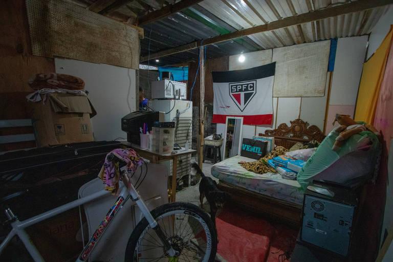 Barraco de madeira com teto de metal guarda bicicleta, cama, caixa com cobertor, geladeira e bandeira do São Paulo