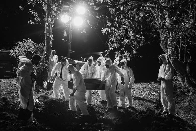 Sepultadores usando trajes de proteção carregam caixão com vítima de Covid-19, iluminados por holofotes no Cemitério Vila Formosa, na zona leste da cidade