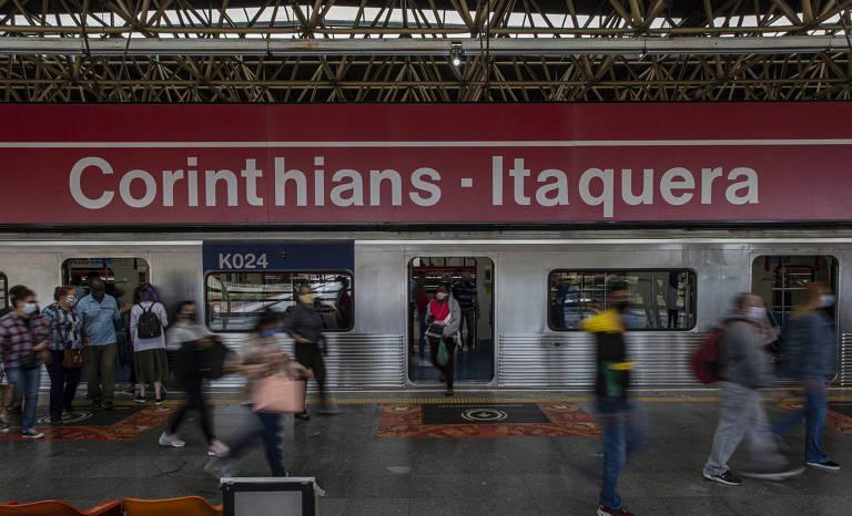 """Trem com vagões com as portas abertas, com pessoas circulando na plataforma e uma placa vermelha com letras brancas no alto com o nome """"Corinthians - Itaquera"""""""