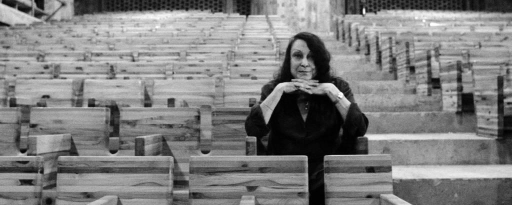 Lina Bo Bardi em meio a cadeiras de madeira