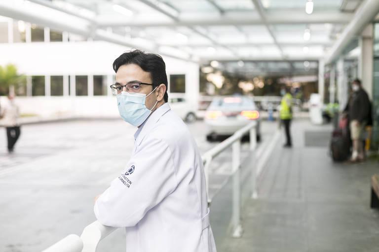 Homem de jaleco branco, máscara, óculos e cabelos escuros em frente ao hospital