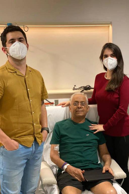Homem de máscara e camisa amarela e mulher de máscara e blusa vermelha em pé ao lado de homem de camiseta verde, sentado, em quarto hospitalar