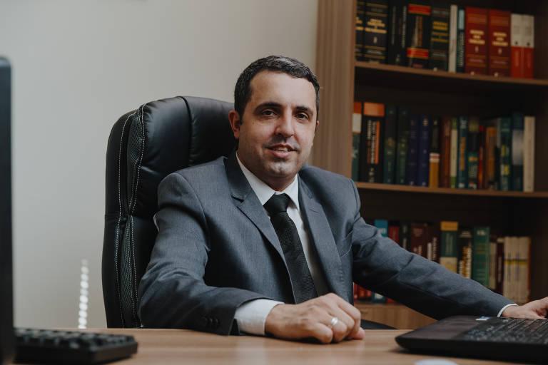 Sentado, o advogado Caio Peres de Souza, 31, em seu escritório em São Miguel Paulista, no extremo da zona leste de São Paulo