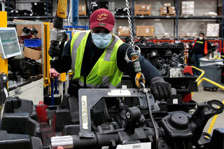 FILE PHOTO: A Dana In. assembly technician wears a face mask as he works to assemble axles for automakers, amid the coronavirus disease (COVID-19) outbreak, in Toledo