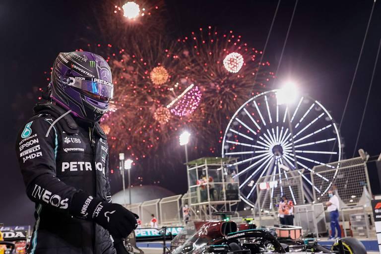 Hamilton, de capacete, sai do carro no Bahrein; fogos de artifício colorem o céu escuro e há uma roda-gigante ao fundo