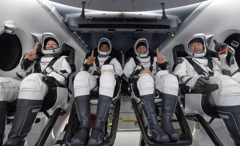 Os quatro astronautas estão sentados presos às cadeiras dentro da cápsula, de interior branco. Eles posam para a foto com o dedo indicador para o alto