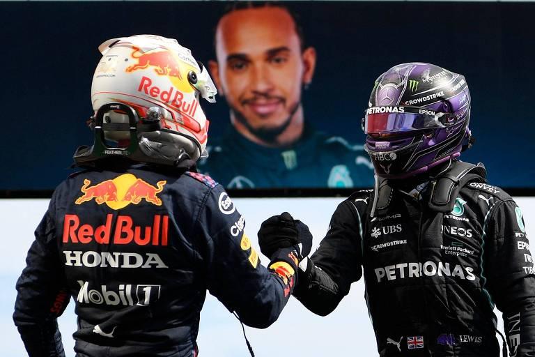 Pilotos se cumprimentam ainda de capacete, enquanto foto de Hamilton aparece em telão