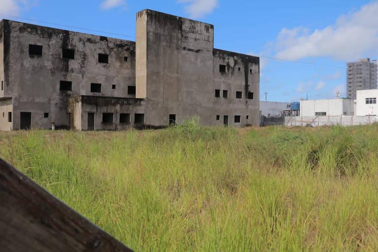 Imagem mostra prédio inacabado, sem portas, janelas ou pinturas, com mato à frente