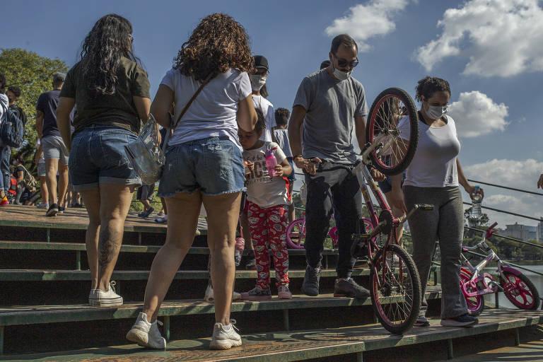 Pessoas em escadaria carregam bicicleta
