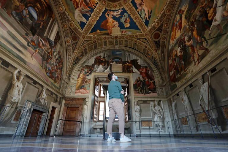 Homem observa afrescos em teto de capela