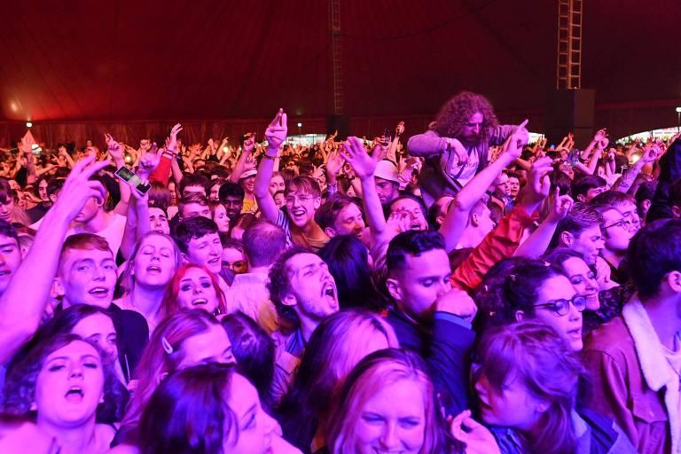 Milhares de pessoas juntas, lado a lado, cantam e dão risada. Todos sem máscara facial