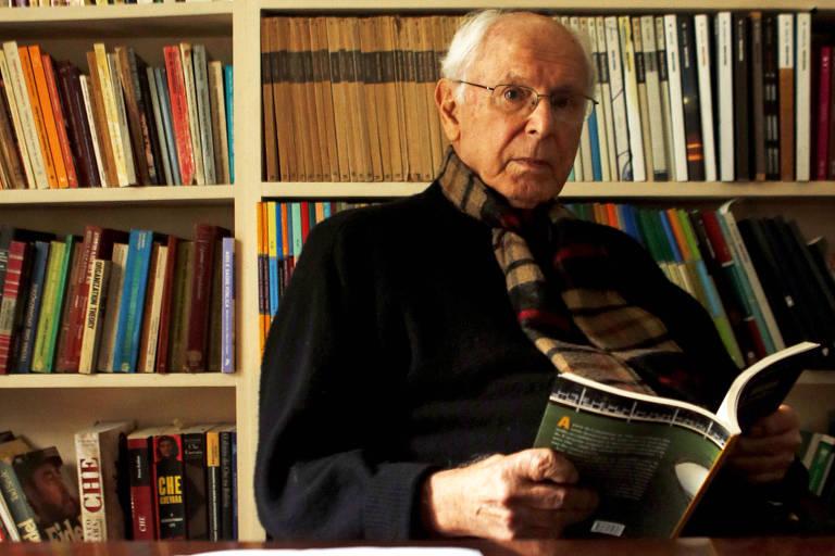 Homem branco de cabelos grisalhos, calvo, veste casaco e cachecol. Está sentado, segura livro aberto e olha para câmera. Ao fundo estante de livros cobre toda parede visível.