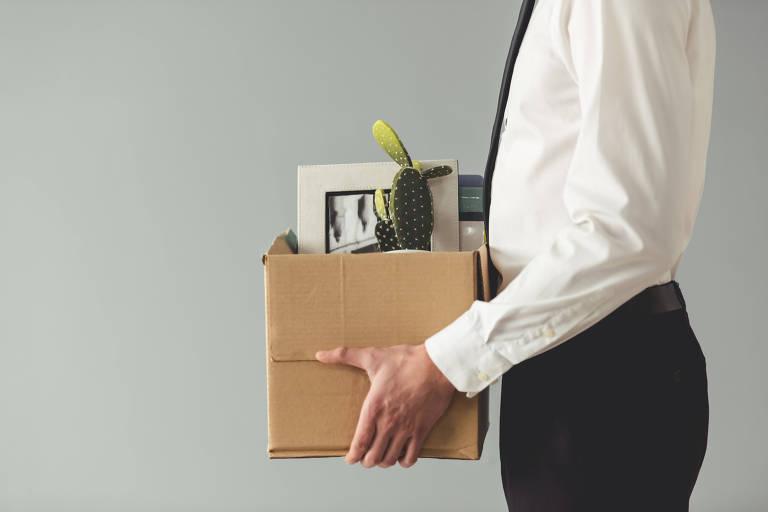 Imagem recortada de um homem branco com roupa formal segurando uma caixa com suas coisas, em fundo cinza.