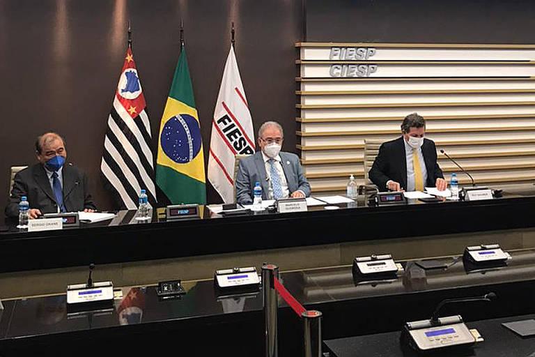 A foto mostra uma bancada vista a certa distância; nela, há três homens sentados. Queiroga é o do meio, de terno cinza e máscara. Atrás dele estão as bandeiras de São Paulo, Brasil e Fiesp