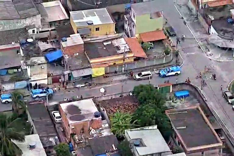 Imagem aérea mostra imóveis baixos vistos do alto. Na área central da foto aparece a rua do bar onde houve a chacina, com carros estacionados na via