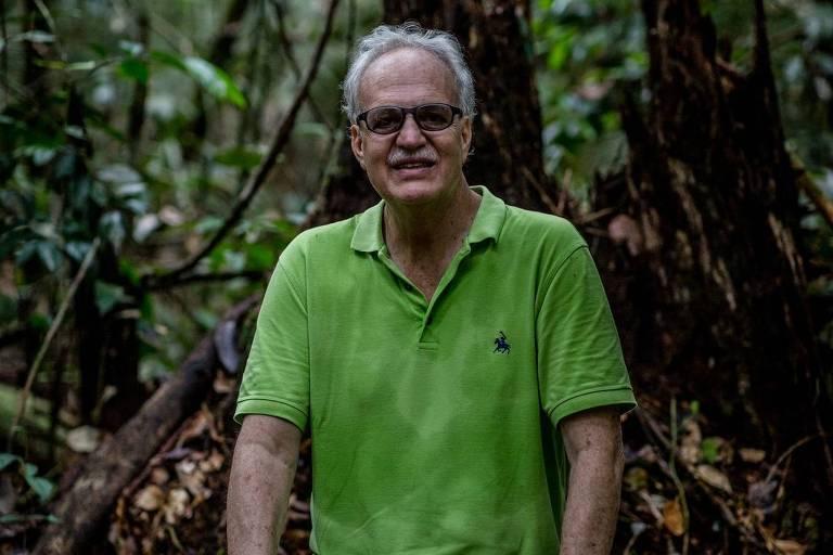 homem idoso está sentado no meio da floresta; usa blusa polo verde claro, calça jeans e óculos enquanto sorri