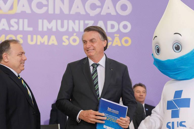 À esquerda, Pazuello, de terno e de perfil; ao meio, o presidente Bolsonaro, de terno, ambos sem máscara; e à direita, o personagem Zé Gotinha, fantasia branca com cabeça em forma de gota, máscara azul e símbolo do SUS no peito
