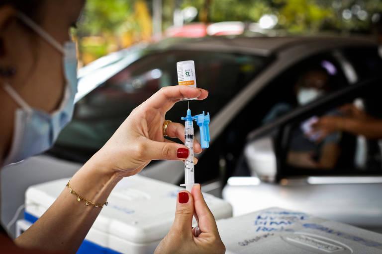 Em primeiro plano, enfermeira de máscara segura seringa e frasco de vacina; ao fundo, carro em que pessoa é vacinada