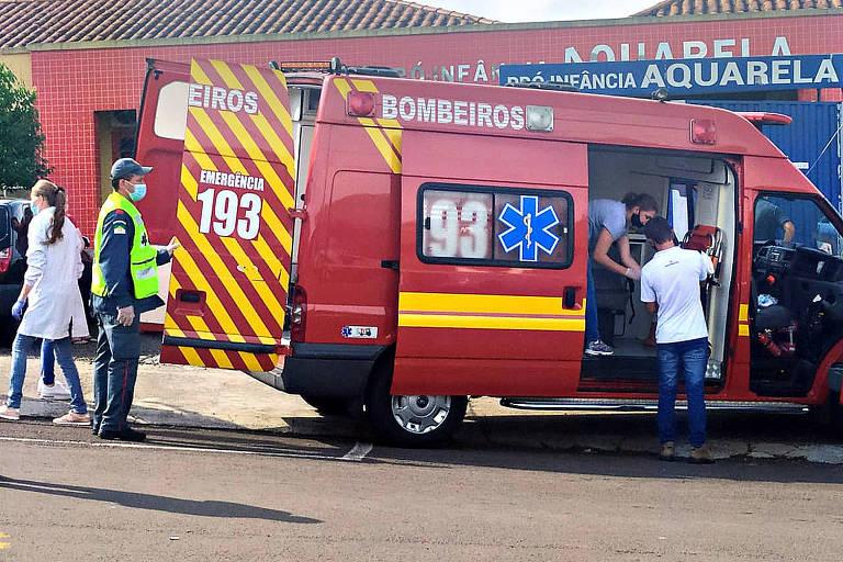 Ambulância vermelha de resgate com a porta aberta e duas pessoas entrando
