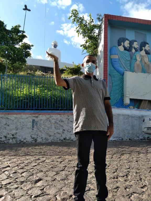 Homem de máscara posa em frente a estátua de padre Cícero em Juazeiro do Norte, no Ceará