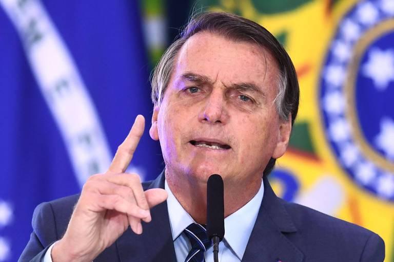 Foto mostra ombros e rosto de Bolsonaro. Ele veste terno e gravata e está falando, e gesticula com a mão com dedo indicador apontado para cima, ao fundo bandeira do Brasil