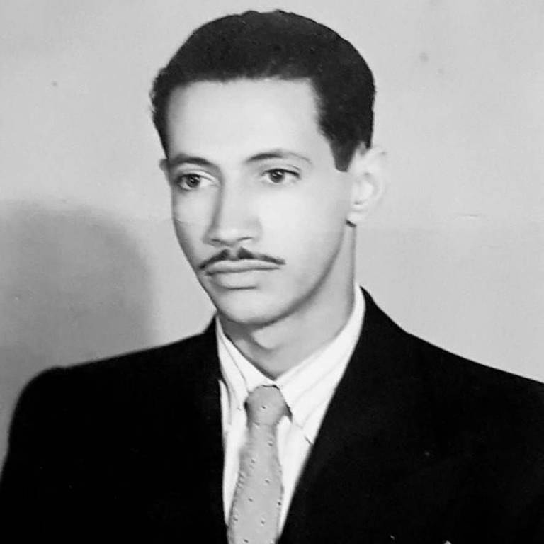 Retrato em preto e branco, antigo, de jovem magro com bigode fino no rosto. ele veste terno e posa para a foto