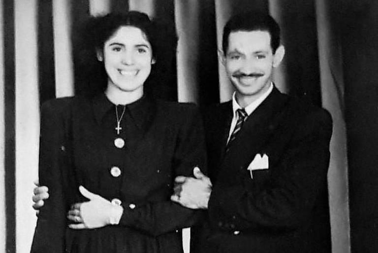 retrato em preto e branco de casal vestido formalmente e posando para foto; os dois estão sorrindo