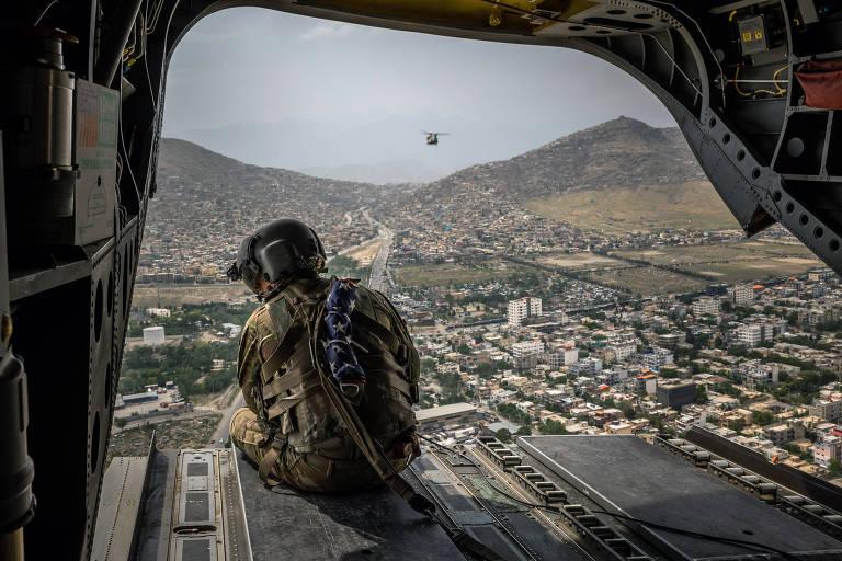 Soldado americano a bordo de helicóptero militar sobrevoa Cabul, capital do Afeganistão