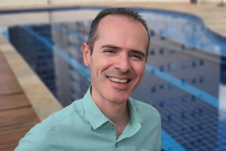 Marcos sorri para foto em frente a uma piscina