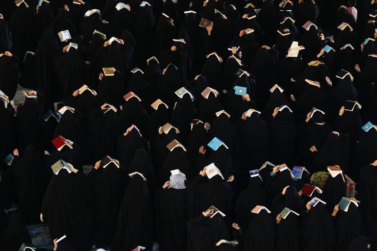 De costas, um grupo de pessoas usando roupa preta segura livros sobre a cabeça.