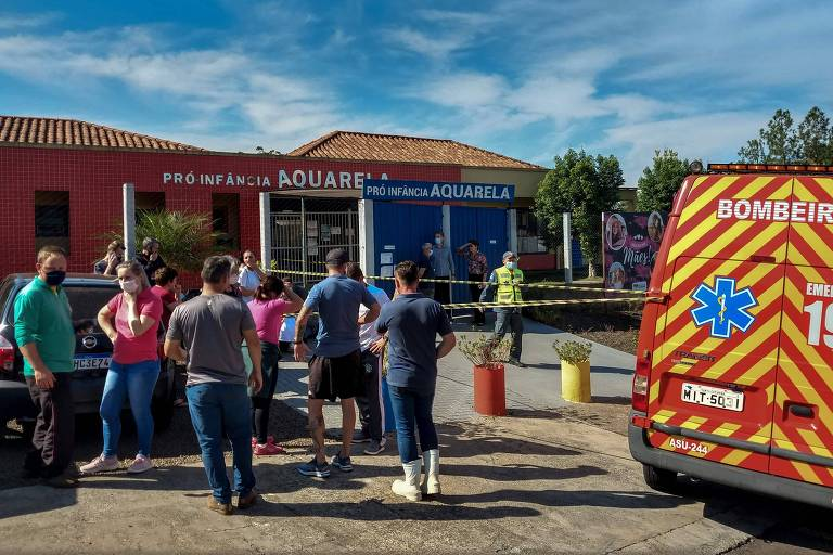 Bombeiros e moradores em frente à escola Pró-Infância Aquarela, alvo de ataque em Saudades (SC)