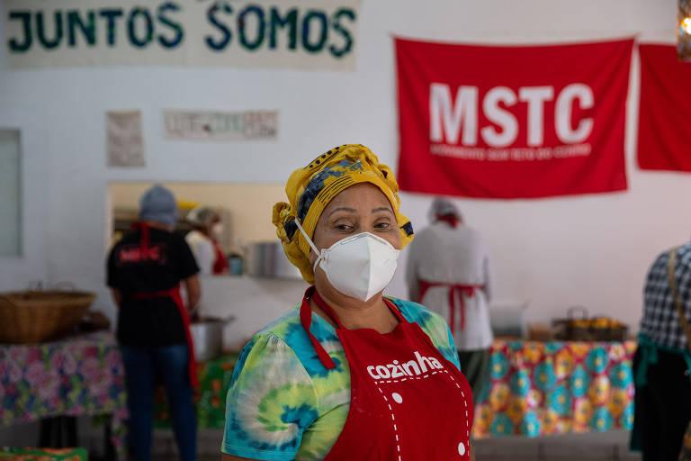 Carmen Silva, líder do Movimento Sem Teto do Centro, posa para foto na cozinha da Ocupação 9 de Julho; ao fundo, dois colaboradores preparam marmitas