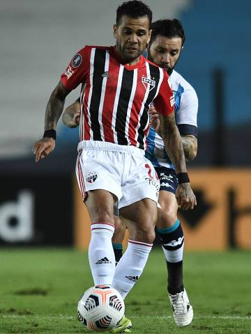 Brazil's Sao Paulo Dani Alves (L) and Argentina's Racing Club Chilean Eugenio Mena vie for the ball during their Copa Libertadores football tournament group stage match at the Presidente Juan Domingo Peron Stadium in Avellaneda, Buenos Aires Province, on May 5, 2021. (Photo by Marcelo ENDELLI / POOL / AFP)