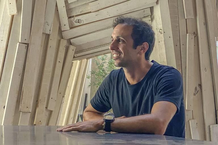 homem de camiseta escura sorri olhando para o lado, ao fundo há tábuas de madeira