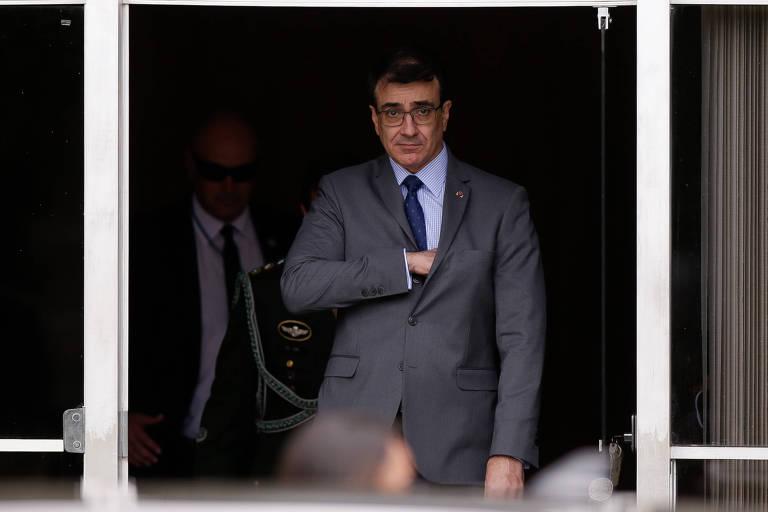 O ministro sai por uma porta de vidro; ele está de terno cinza e coloca a mão direito num bolso interno do paletó