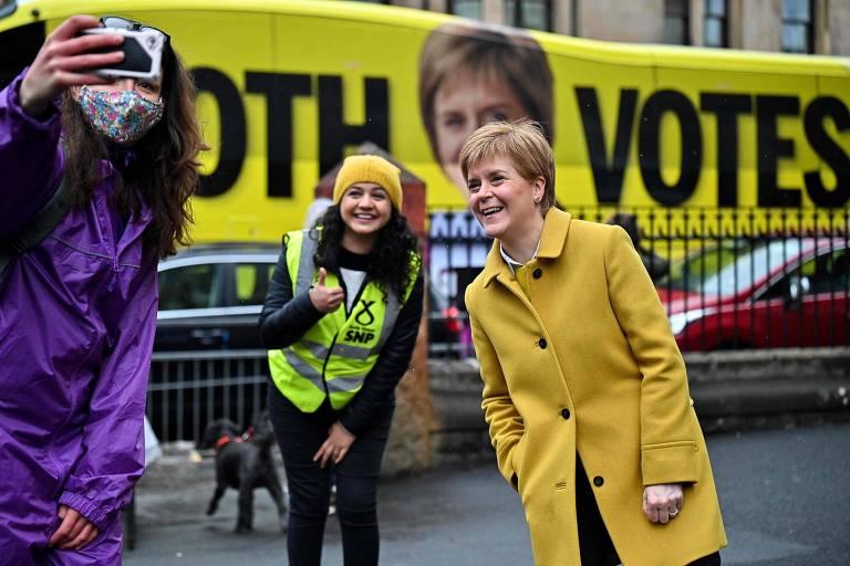 Mulher de casaco comprido cor de mostarda sorri para celular que moça de máscara segura no canto esquerdo da imagem; ao fundo, uma faixa de campanha eleitoral