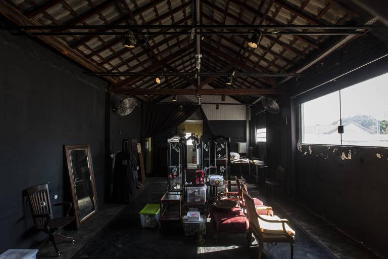 Galpão com móveis, espelhos e cenografia montadas; há uma janela do lado esquerdo
