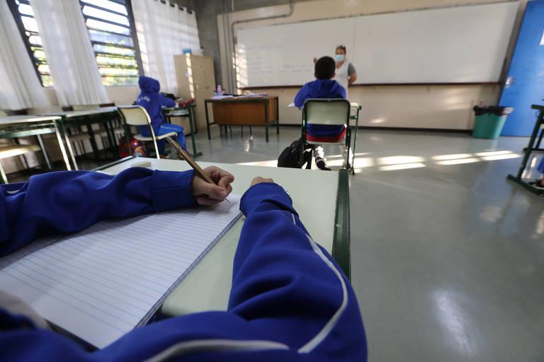 Dentro de uma sala de aula, imagem em close mostra os braços de uma criança sentada em uma carteira escolar apoiando os braços sobre a mesa e escrevendo em um papel.
