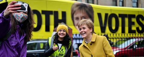 Scotland's First Minister and leader of the Scottish National Party (SNP), Nicola Sturgeon (R)) and candidate Roza Salih (C) pose for a selfie with a voter at Annette Street school polling station in Glasgow, Scotland on May 6, 2021, as voters go to the polls for the Scottish Parliament election. (Photo by Jeff J Mitchell / POOL / AFP) ORG XMIT: 775652067