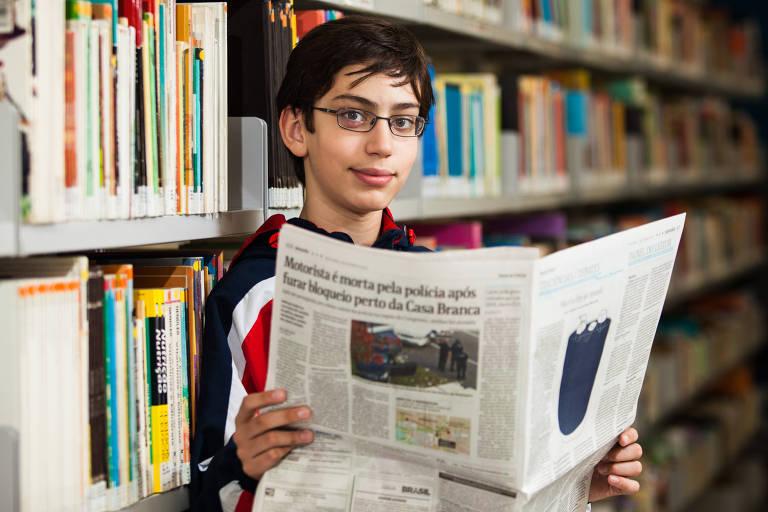 Adolescente olha para câmera enquanto segura um exemplar impresso da Folha de S.Paulo