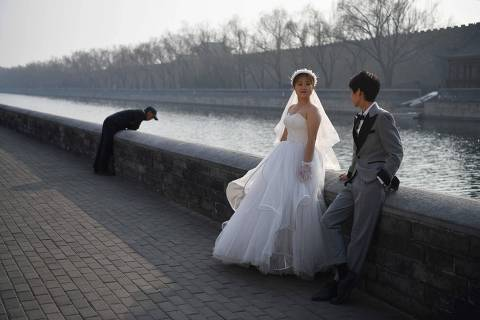 A couple poses for wedding photos beside the moat which surrounds the Forbidden City in Beijing on February 26, 2021. (Photo by GREG BAKER / AFP)