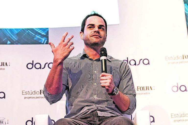 Alexandre está sentado, gesticulando com a mão direita e, na esquerda, segurando o microfone; atrás, há um painel branco com marcas estampadas