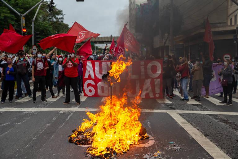 Manifestantes fazem barreira sobre uma faixa de pedestre no meio da avenida Tiradantes e acendem fogueira no meio da pista