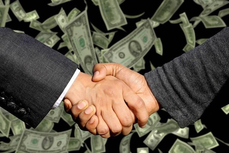 Homens brancos, de terno, cumprimentando-se com um aperto de mão. Ao fundo, notas de dólar caem