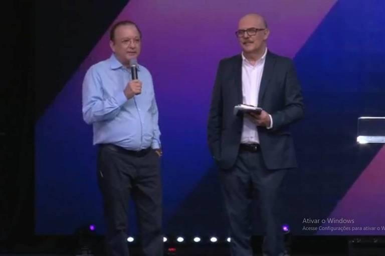 Pastor está à esquerda, de camisa azul e microfone na mão, e o ministro, de terno e sem gravata, está à direita.