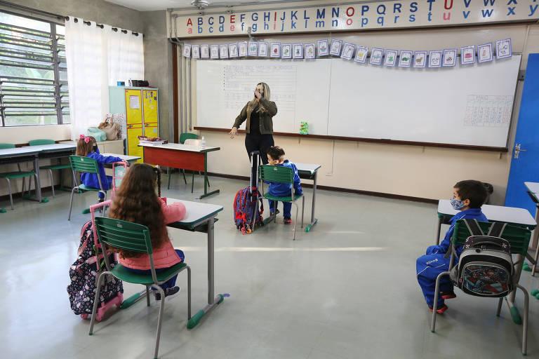 Alunos em carteiras distanciadas enquanto professora fala em frente a lousa branca