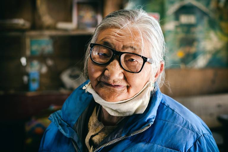 Idosa asiática veste óculos e máscara no queixo, sorrindo para a câmera