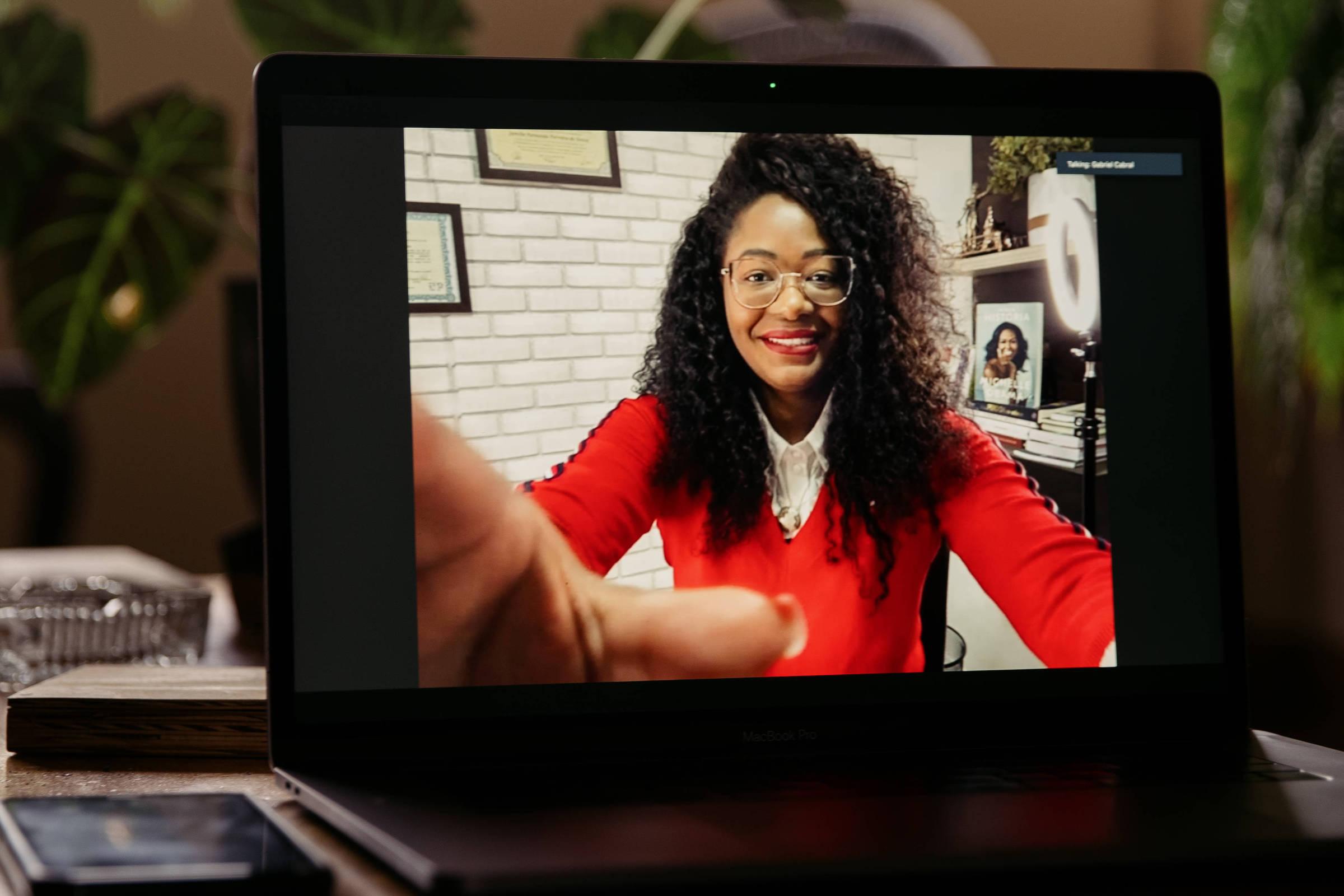 Tela de computador onde de vê mulher negra que sorri e segura tela do aparelho que a filma, ao fundo ambiente de escritório